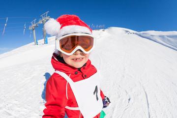 Cute skier in Santa's hat having fun at snowy hill