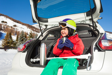 Little skier sitting in car boot and drinking tea