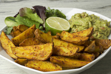 Spicy potato wedges with guacamole, green salad and lime