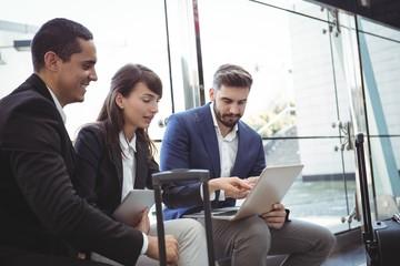 Business executives using laptop on platform