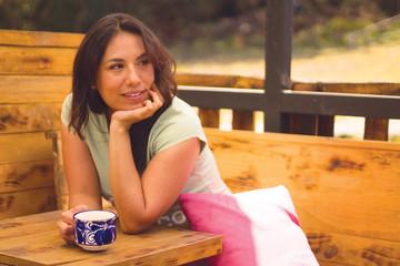 Mujer tomando café en cabaña