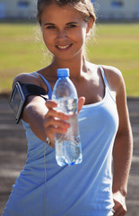 Young beautiful sports girl with water during jogging
