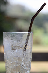 Glass of iced water with plastic straw.