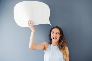 Have you say!  Beautiful woman standing against a grey background and holding a speech bubble