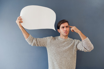 Handsome man holding a blank field of white copy space shaped like a speech bubble.