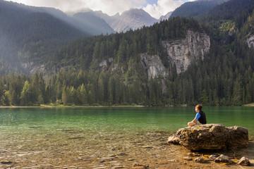 Child looks Tovel lake and the Brenta's dolomites, Trentino, Italy