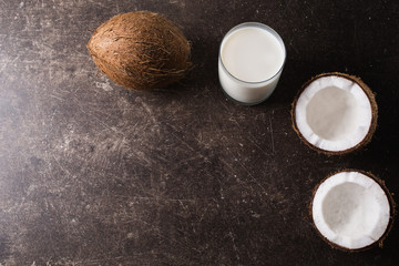 Coconut and coconut milk on a dark marble background. Exotic large walnut. Personal care. Spa treatments