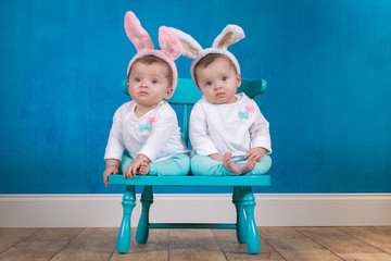 Adorable identical twin baby girls wearing bunny ears
