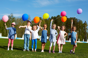 Big group of happy children with balloons on the outdoors