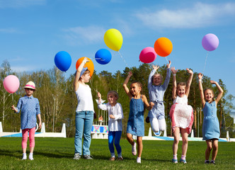 Big group of happy children jump with balloons on the outdoors