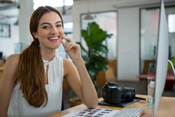 Smiling female graphic designer sitting at desk