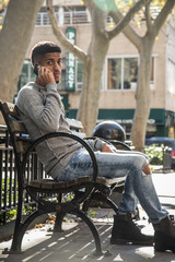 A young, black man talks to on the phone in a NYC park