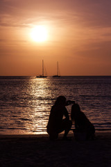 Silhouettes of people in sunset. A couple in the dusk looking at the boats in the ocean. Vertical outdoors shot.