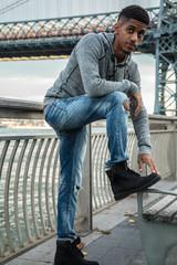A portrait of a young, black man along NYC's East River Williamsburg Bridge
