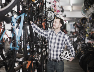 male in bicycle shop chooses for himself sports bike