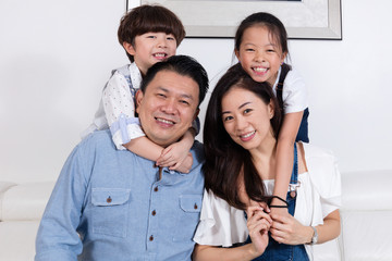 Happy Asian Chinese family sitting on the couch smiling