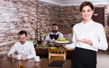 Young woman waiter bringing order for visitors