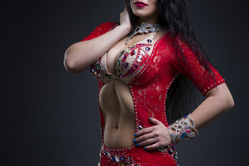 Exotic eastern women performs belly dance in ethnic red dress