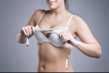 Woman in white underwear measuring breast volume on gray background