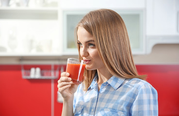 Young beautiful woman with fresh juice in the kitchen