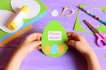 Small child hold a Easter card in hands. Child made Happy Easter greeting card in egg shape. Imagination and creativity for child development. Stationery on a wooden table