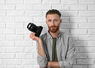 Handsome photographer near light brick wall