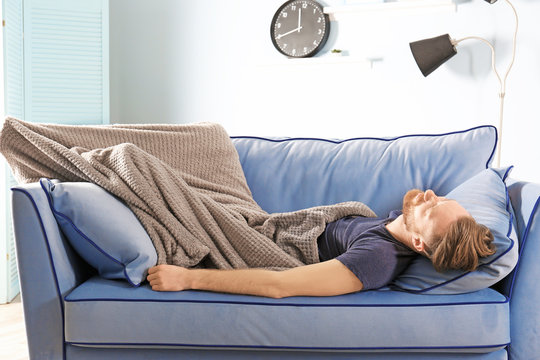 Young man with blanket sleeping on sofa at home