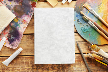 Beautiful notebook, paints and brushes on wooden table