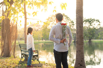romantic man giving red flower to girlfriend in the garden