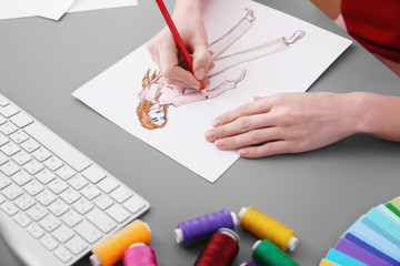Young designer drawing sketch in office, closeup