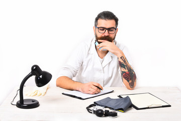 Bearded caucasian doctor sitting at table