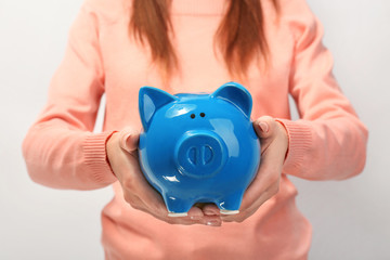 Young woman with piggy bank on light background, closeup