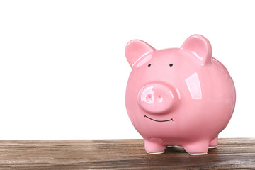 Pink piggy bank on wooden table against white background