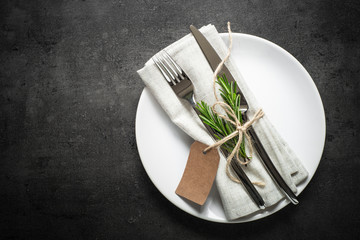 Table setting. Fork knife and white plate at dark slate table.