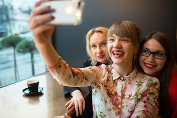 Laughing young ladies taking selfie
