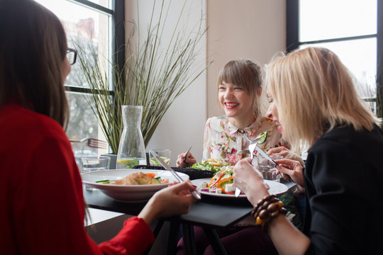 Smiling young women having dinner together