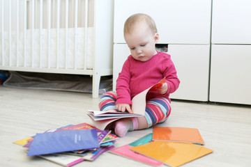 Cute 10 months baby girl reads books at home