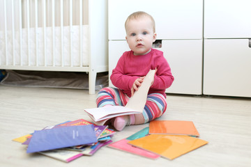 Lovely 10 months baby girl reads books at home