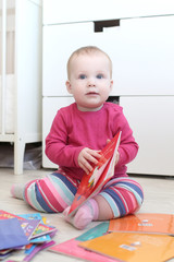 Cute 10 months baby girl with books at home