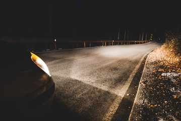 the headlights of a car on mountain road in the night - concept driving safety Wall mural