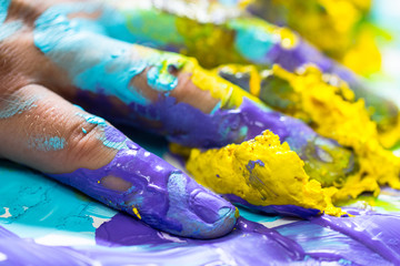 Hand and finger dipped, smudged and stained in beautiful bright blue, purple and yellow paint as creative artist or painter concept background