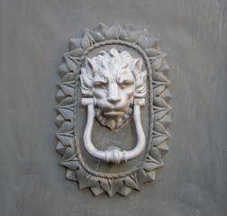 Lion head knocker on an old wooden door in Tuscany, Italy.