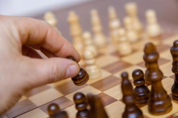 Schachspieler zieht mit schwarzem Bauer. Closeup von Hand, die eine Spielfigur hält