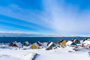 Yellow, blue, red and green inuit houses covered in snow at the fjord of Nuuk city, Greenland