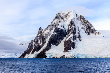 Gigantic steep stone cliff covered with snow and sea in foreground, close to Argentine islands, Antarctica