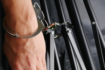 The chrome metal handcuffed bondage on man hand represent the crime and punishment equipment concept related idea.