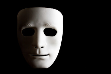 White human face mask on black background.