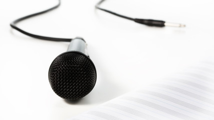 Microphone and music paper on white background, close view