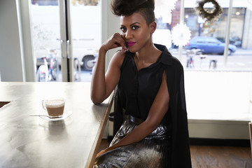 Trendy woman sitting in cafe, looking at camera, horizontal