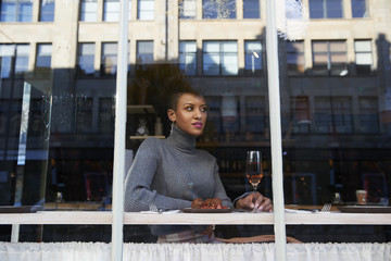 Stylish young woman sitting in cafe seen through window
